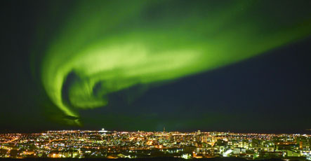 March 2005, Reykjavik, Iceland --- Aurora Borealis over Reykjavik --- Image by © Arctic-Images/Corbis
